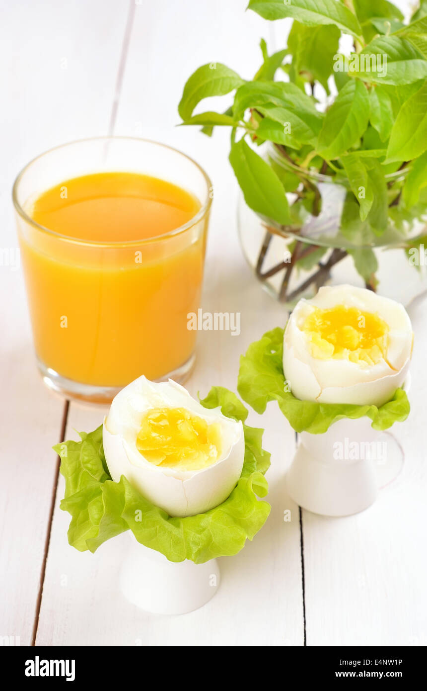 Boiled eggs in egg cups on wooden table - Stock Image