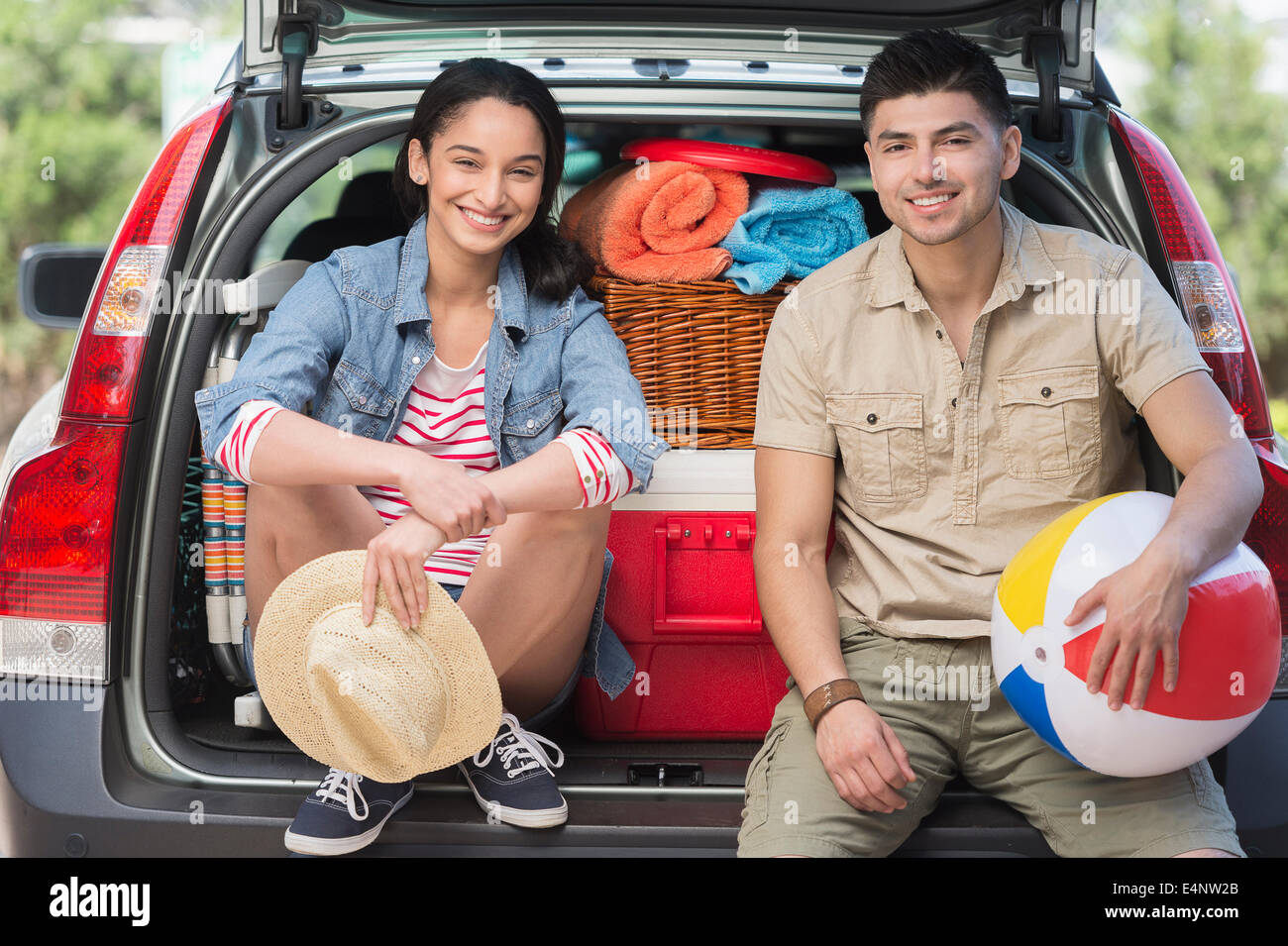 Portrait of young couple sitting in open car trunk - Stock Image