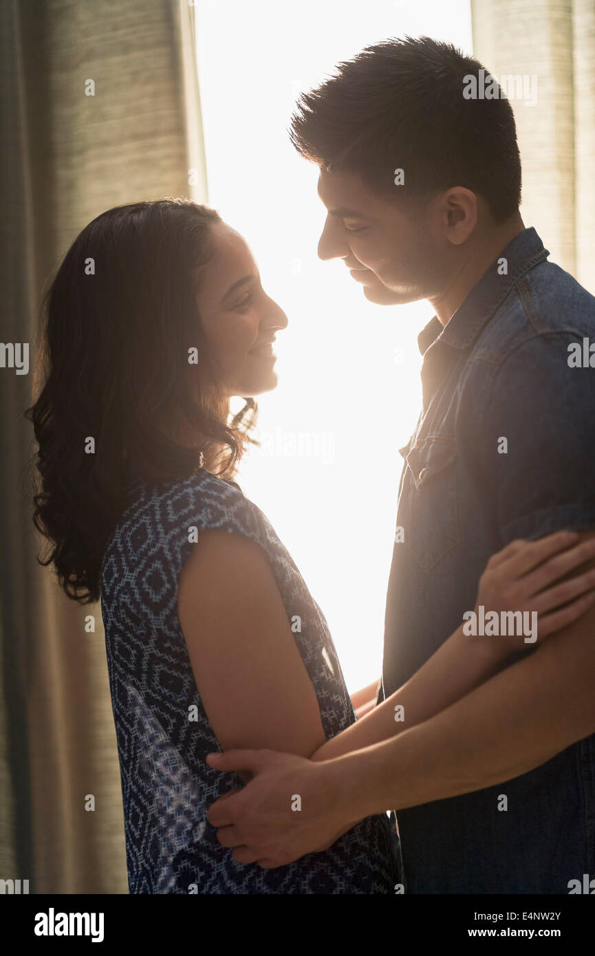 Young couple embracing in sunlight - Stock Image