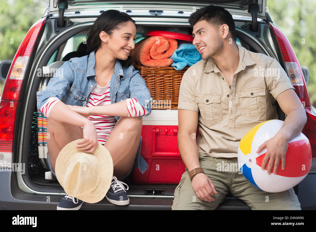 Young couple sitting in open car trunk - Stock Image