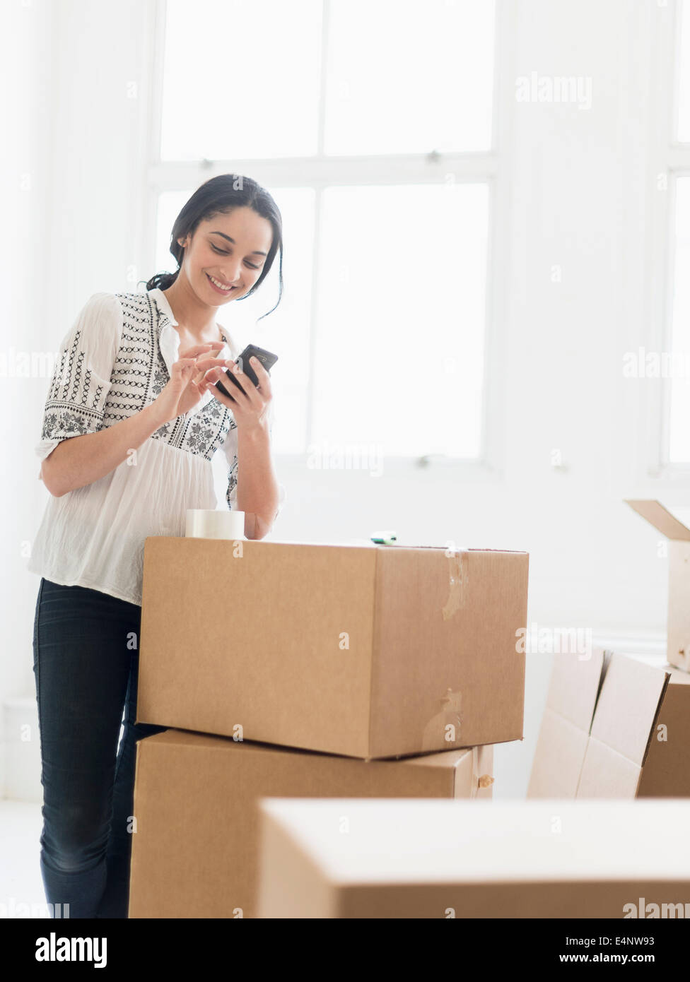 Young woman standing among boxes in new home and using mobile phone - Stock Image