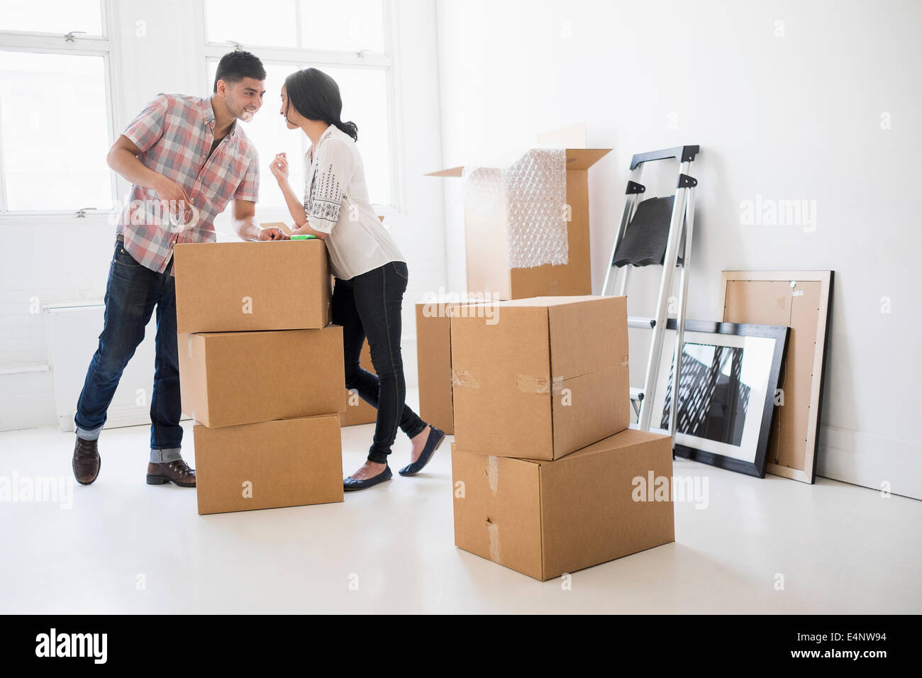 Young couple standing among boxes in new home - Stock Image