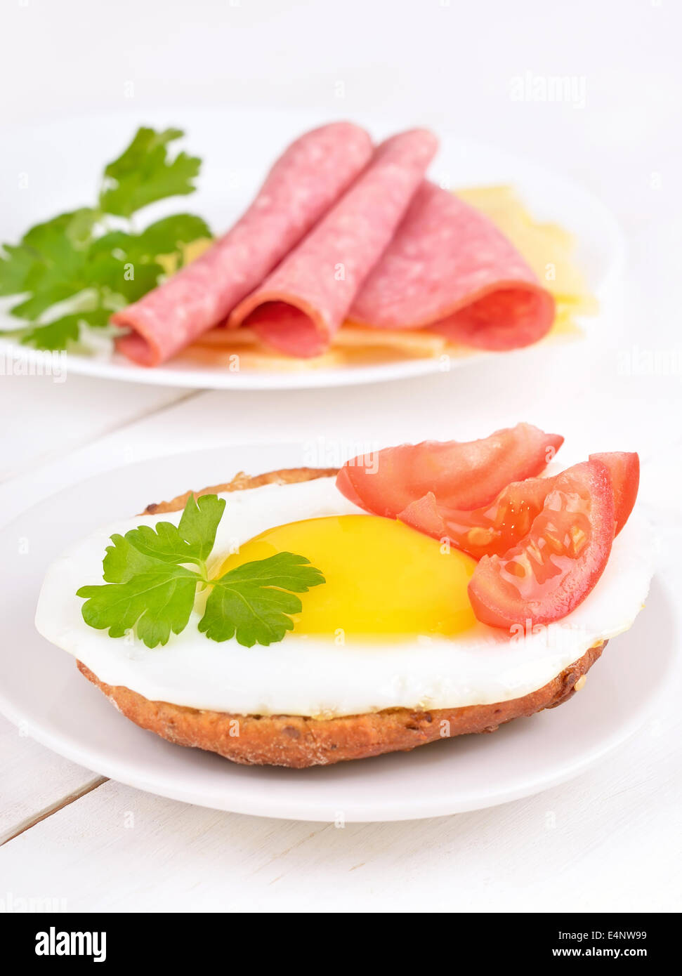 Sandwich with fried egg, tomato slices and parsley on wooden table - Stock Image