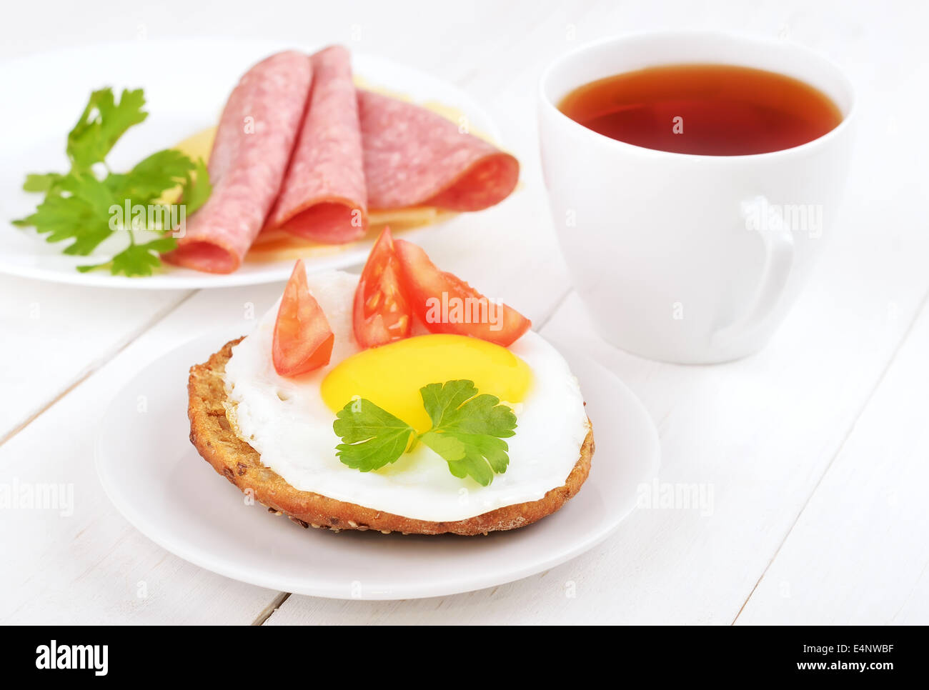 Breakfast - sandwich with fried egg, tomato slices and tea on wooden table - Stock Image