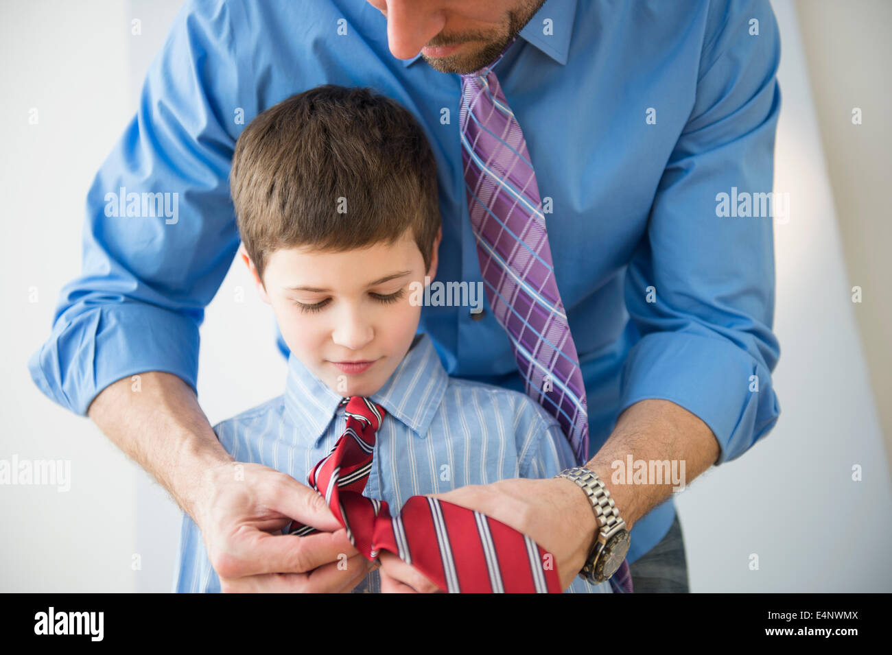 Father adjusting son's (8-9) tie - Stock Image