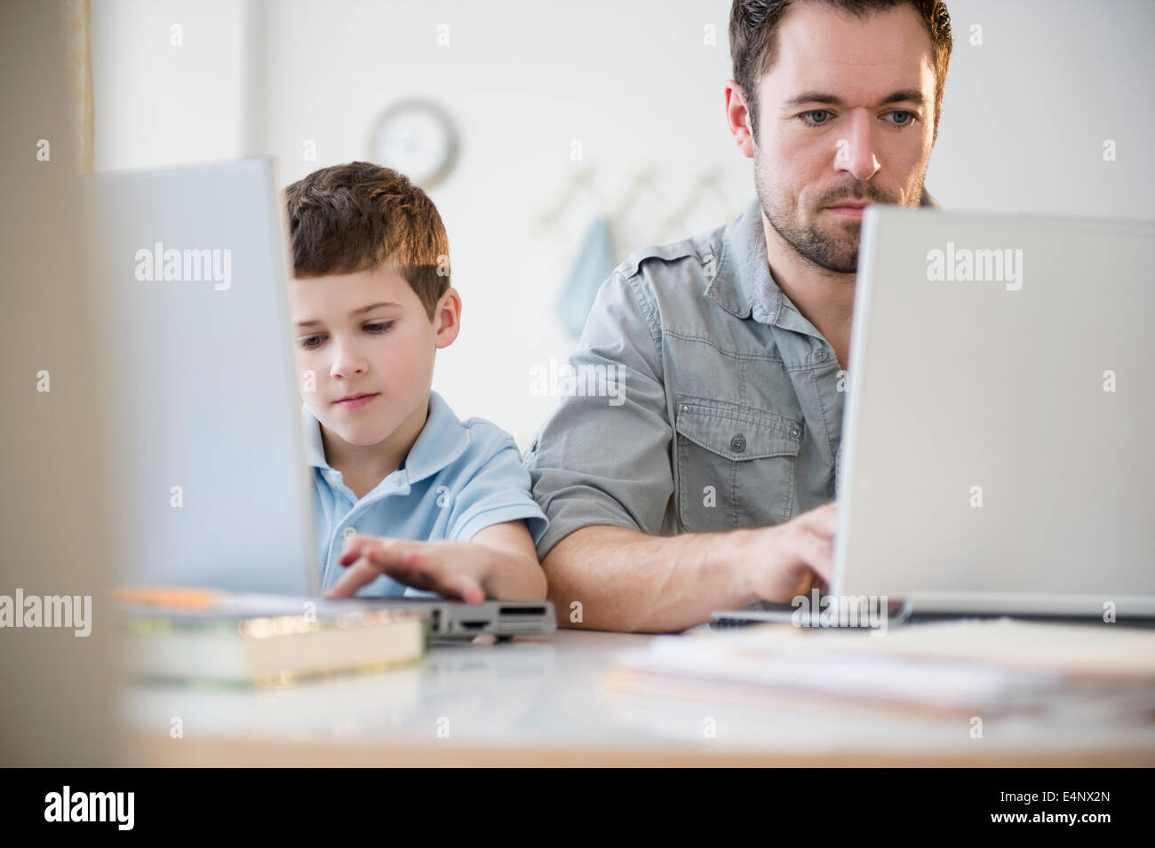 Father and son (8-9) working on laptops - Stock Image