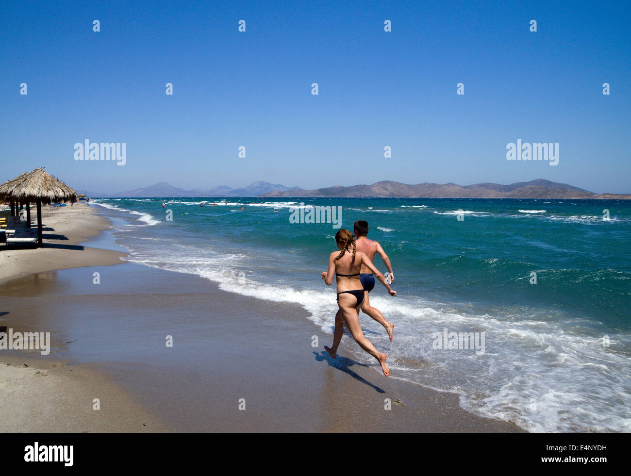 People running along Tingaki Beach, Tingaki, Kos Island, Greece. Stock Photo