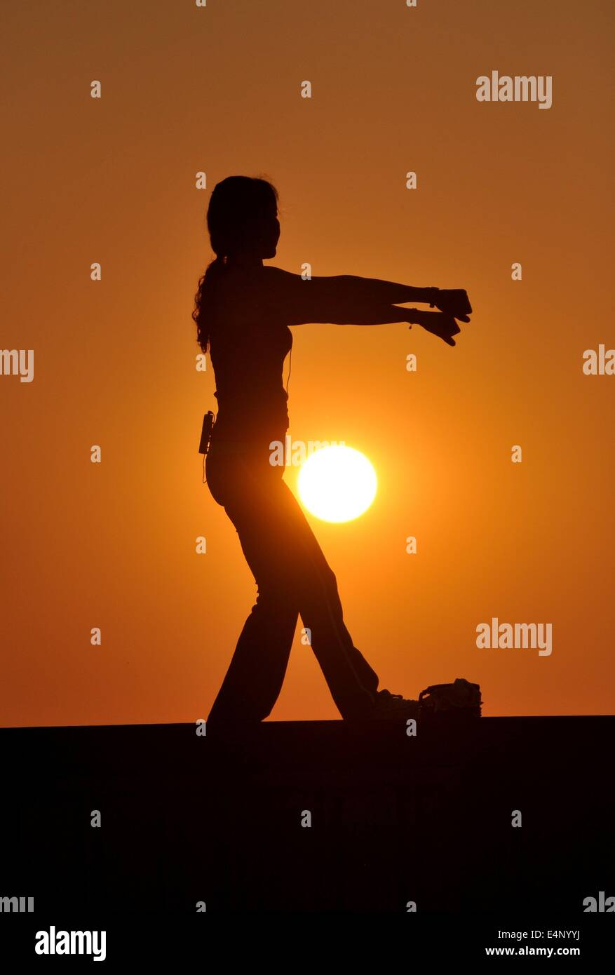 Bang Saen, Thailand:  A tai 'chi instructor standing on a platform silhouetted by the setting sun giving a class - Stock Image