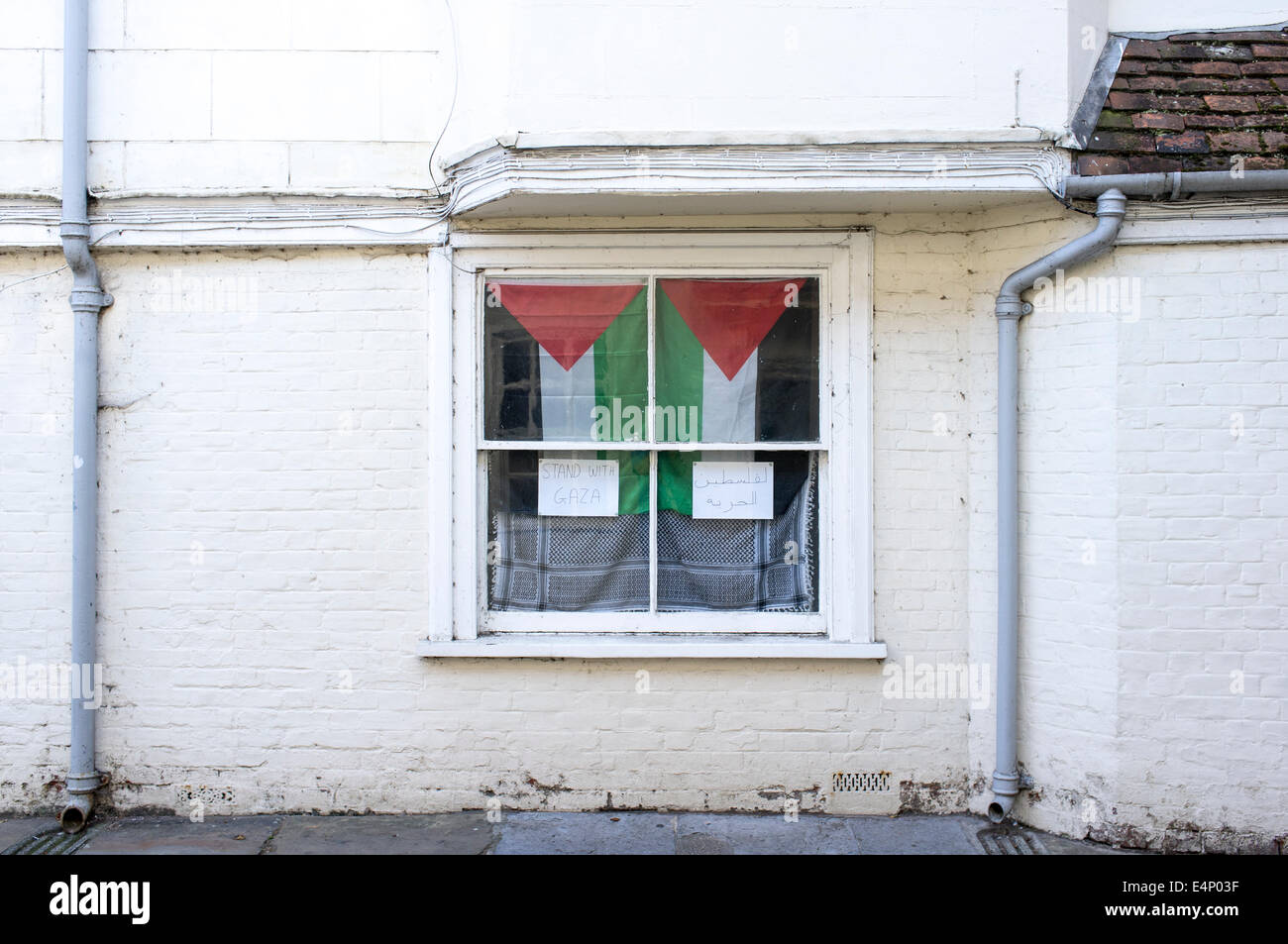 Flag of Palestine hanging in UK window with hand written notice in English and Arabic saying 'stand with Gaza' - Stock Image