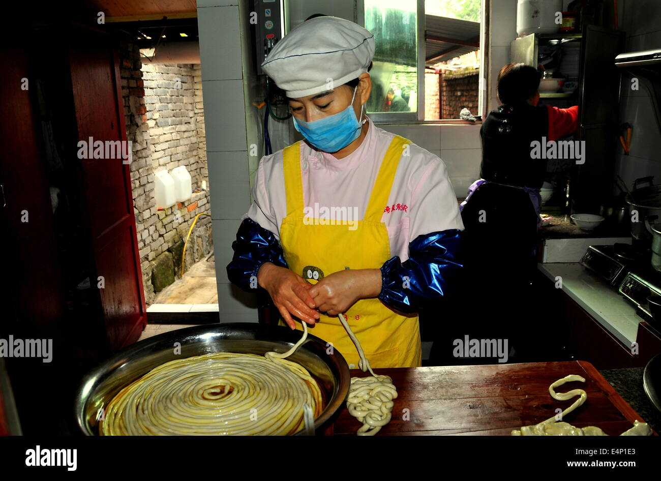 LANGZHONG ANCIENT CITY (SICHUAN), CHINA:  Woman at work in her restaurant's kitchen preparing dough for homemade - Stock Image