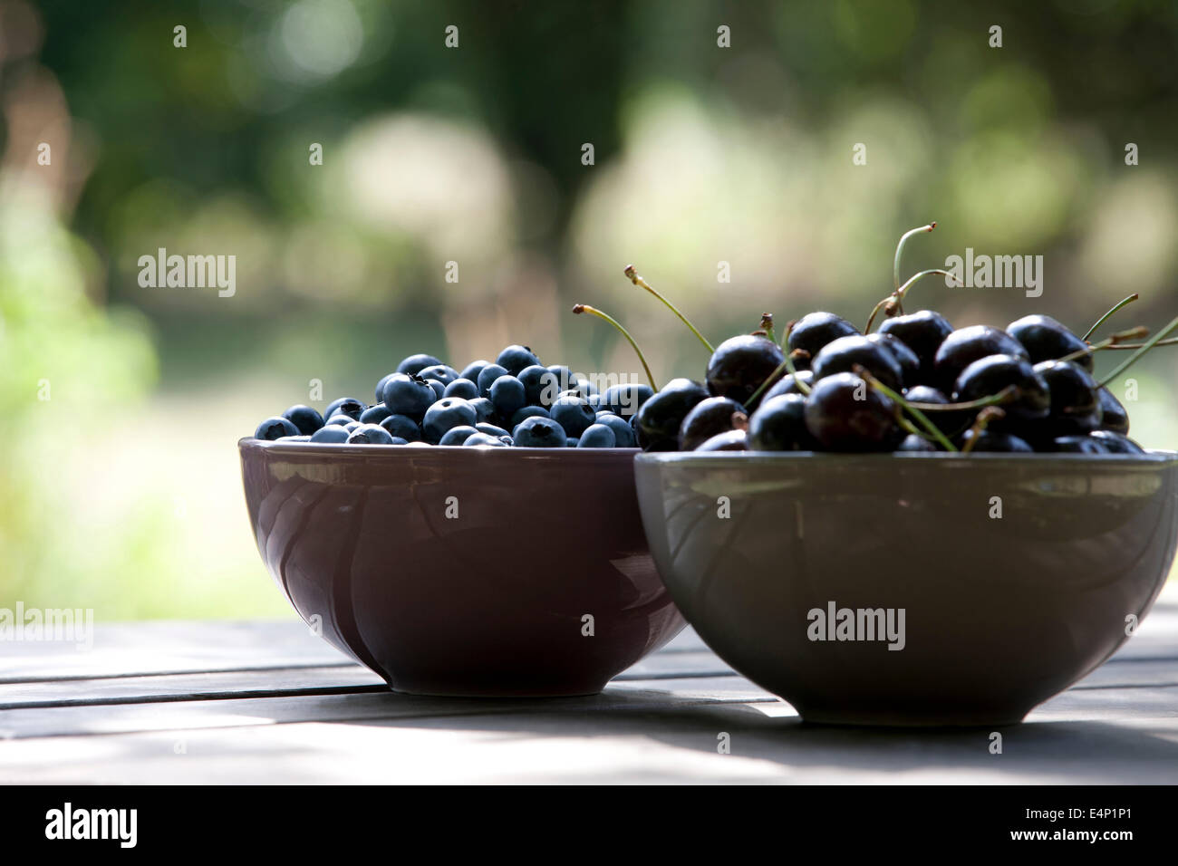 Black cherries and blueberries in ceramic bowls - Stock Image