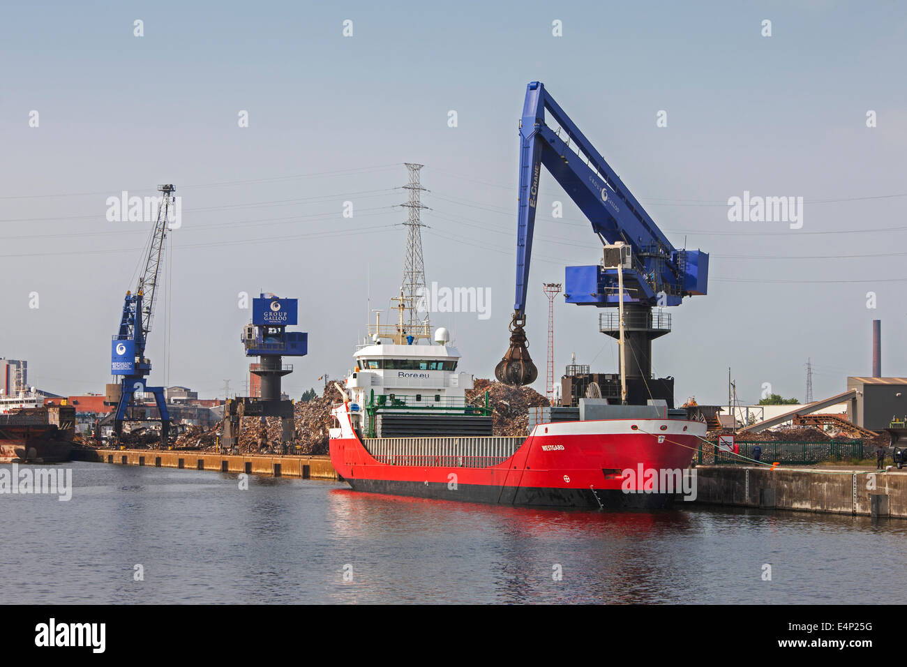 E-Crane, scrap crane loading recycled metal on cargo ship at Van Heyghen Recycling export terminal, port of Ghent, - Stock Image