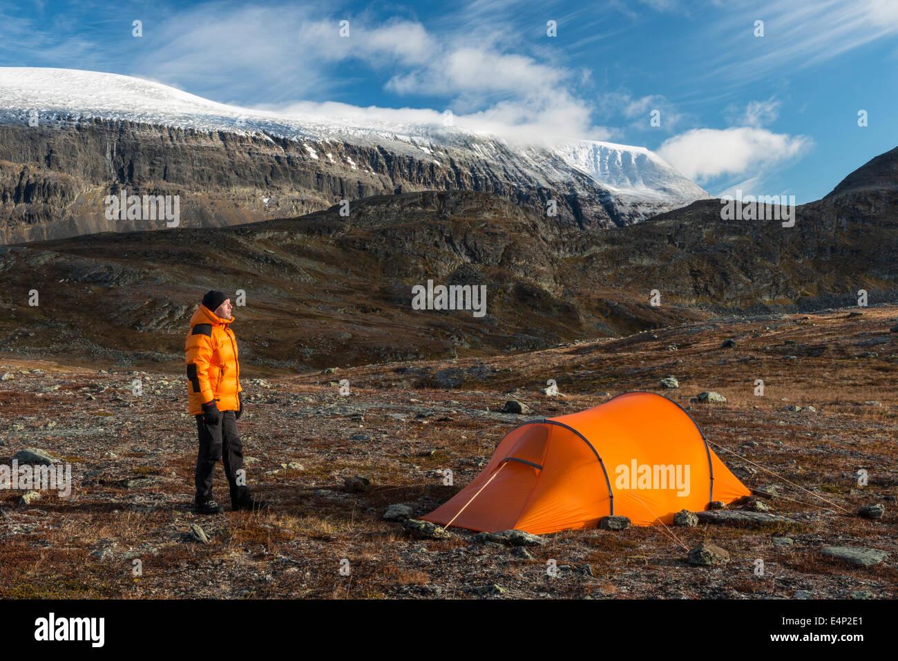 Mann neben Zelt mit Blick auf den Berg Sinnitjohkka, Kebnekaisefjaell, Norrbotten, Lappland, Schweden - Stock Image