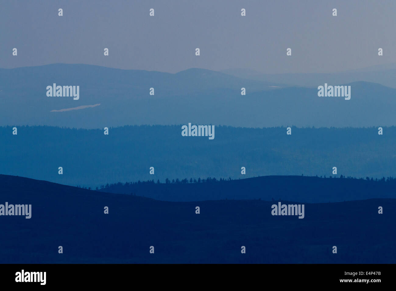 Distant bluish mountains in the Swedish and Norwegian mountain ridge, seen from Grövelsjön, Sweden. Stock Photo
