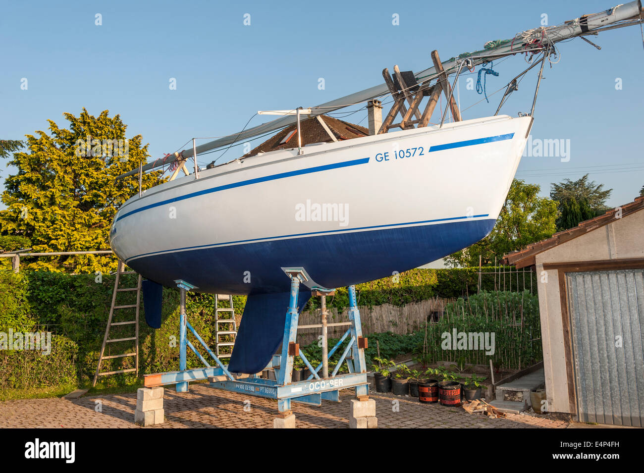 A sailing yacht in a cradle in a boatyard, after being painted with antifouling - Stock Image