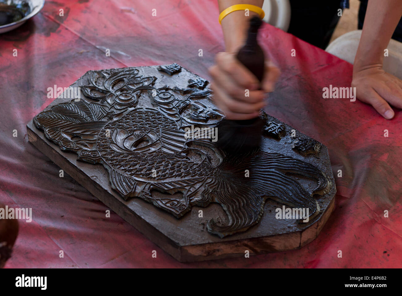 Man demonstrating Chinese woodblock printing at cultural festival - USA - Stock Image