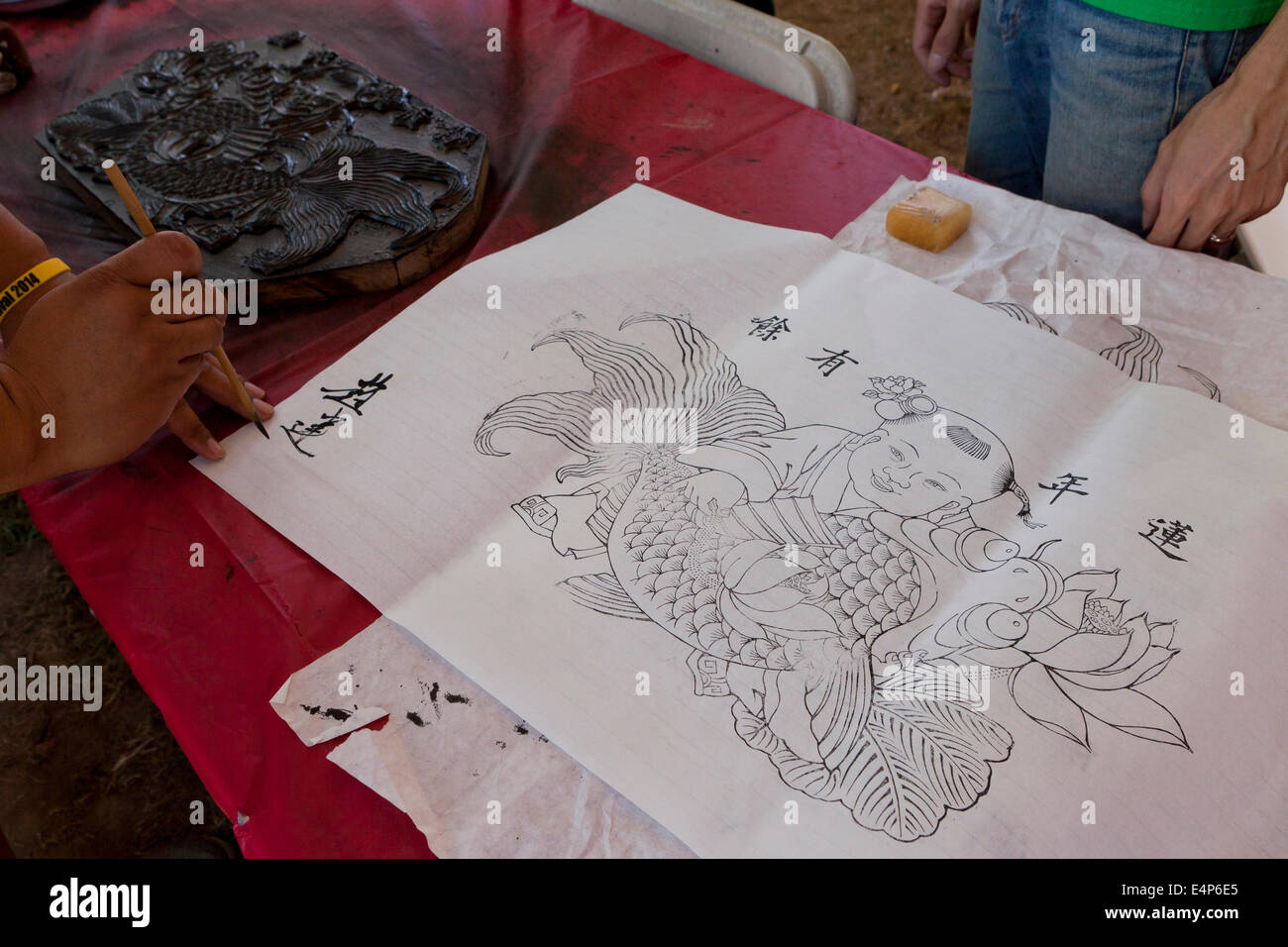 Man signing Chinese woodblock print - Stock Image