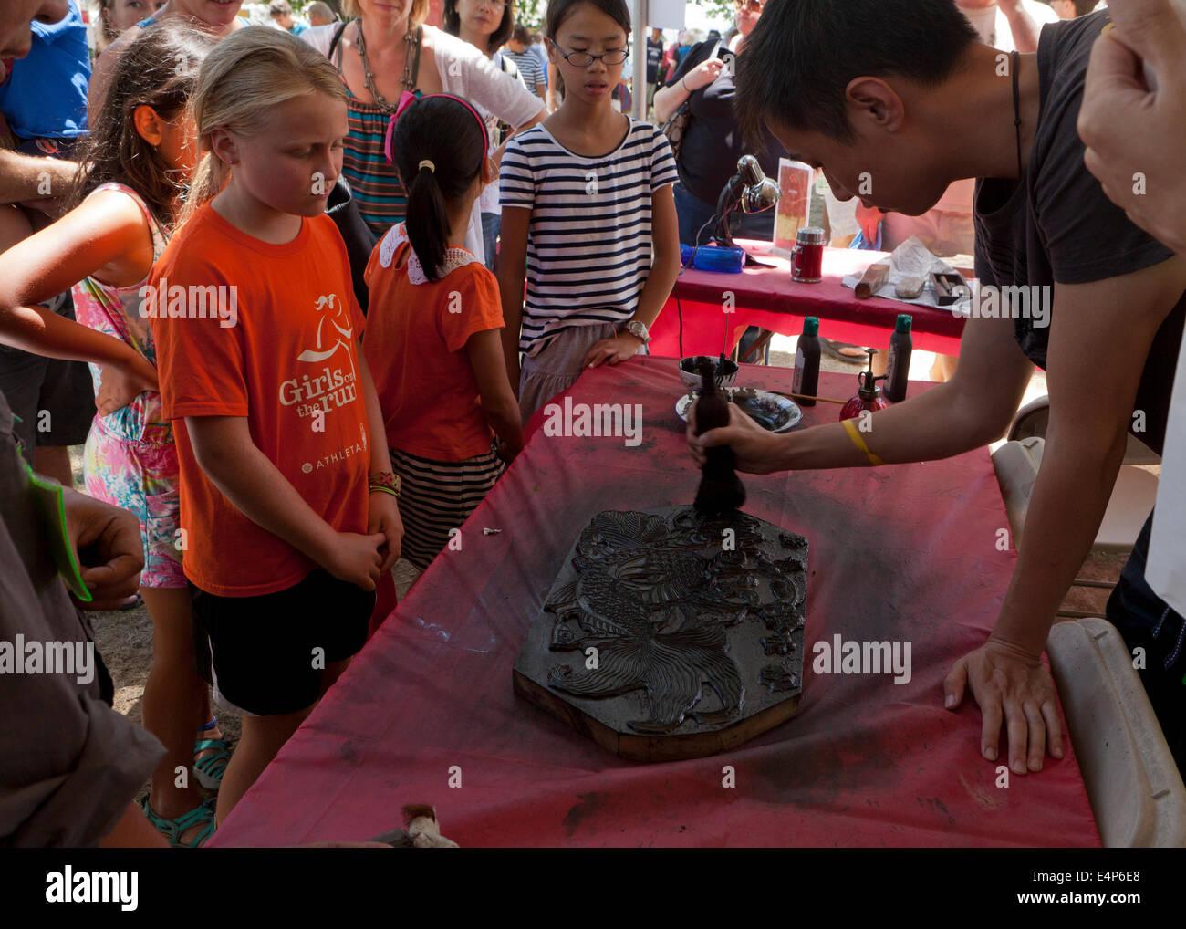 Man demonstrating Chinese woodblock printing at cultural festival - USA - Stock Image