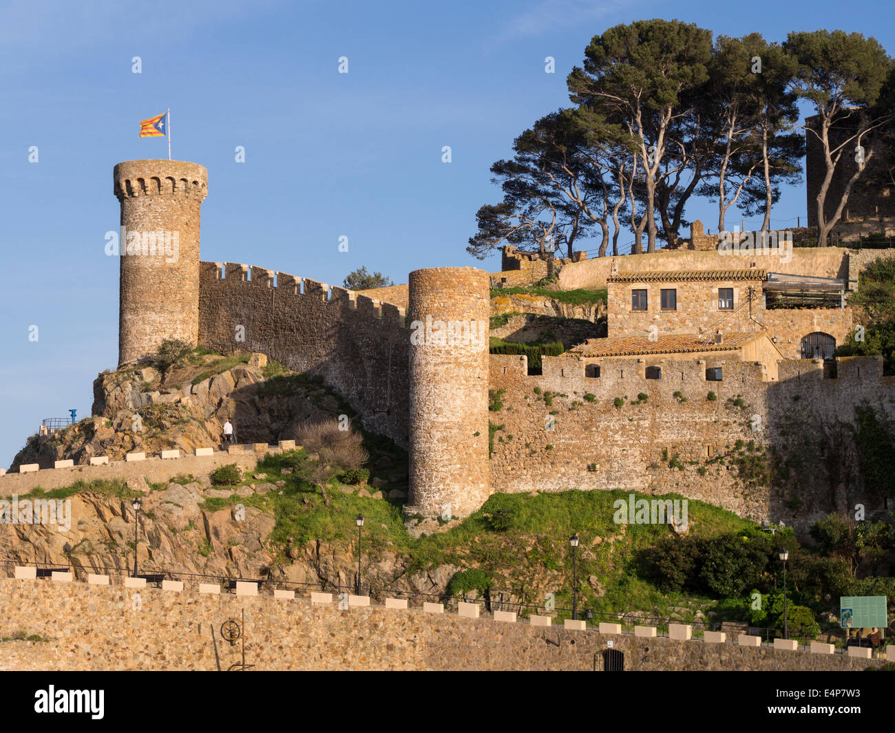 Fortress of Tossa de Mar topped by a Catalonian Flag. The massive stone defensive wall and tower of this coastal - Stock Image