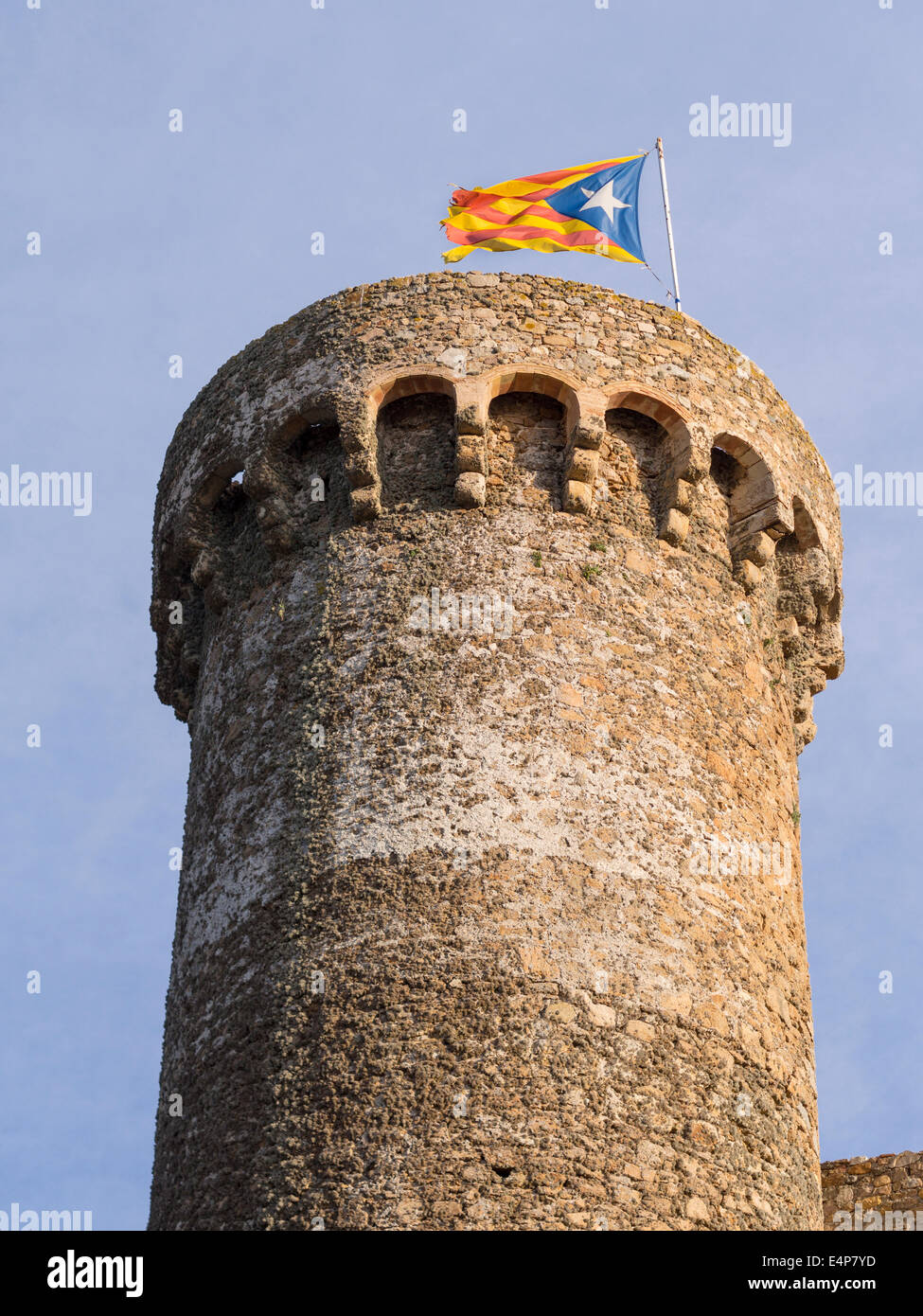 Tower of Tossa de Mar topped by a Catalonian Flag. The massive stone defensive tower of this landmark along the - Stock Image