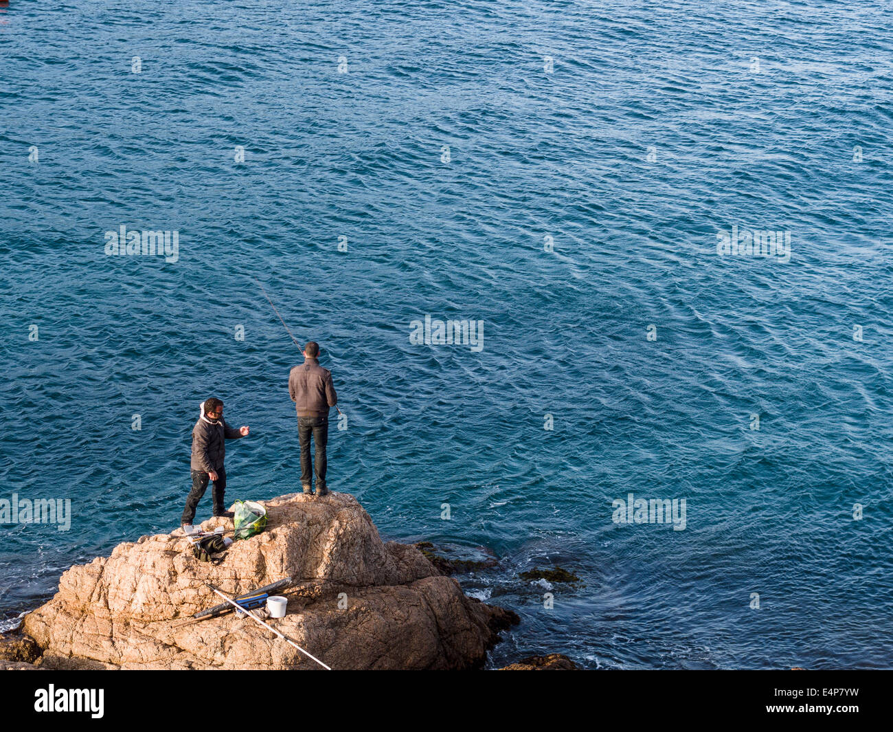 Shore Fishing off the rocks. Two men fish from a rock just below the castle near the shore at Tossa de Mar. - Stock Image