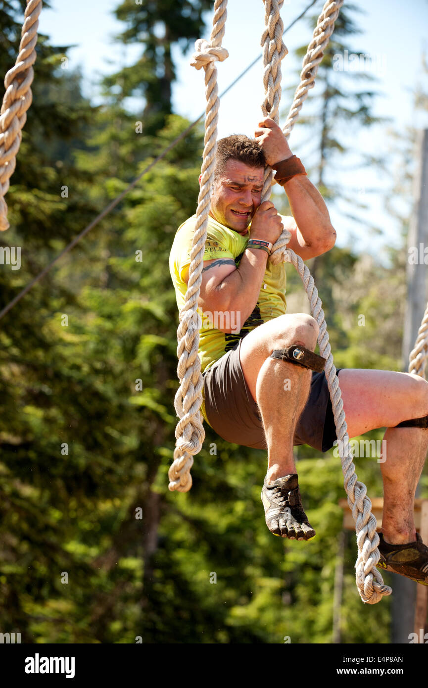 A man on an obstacle at the Whistler Vancouver Tough Mudder event. - Stock Image