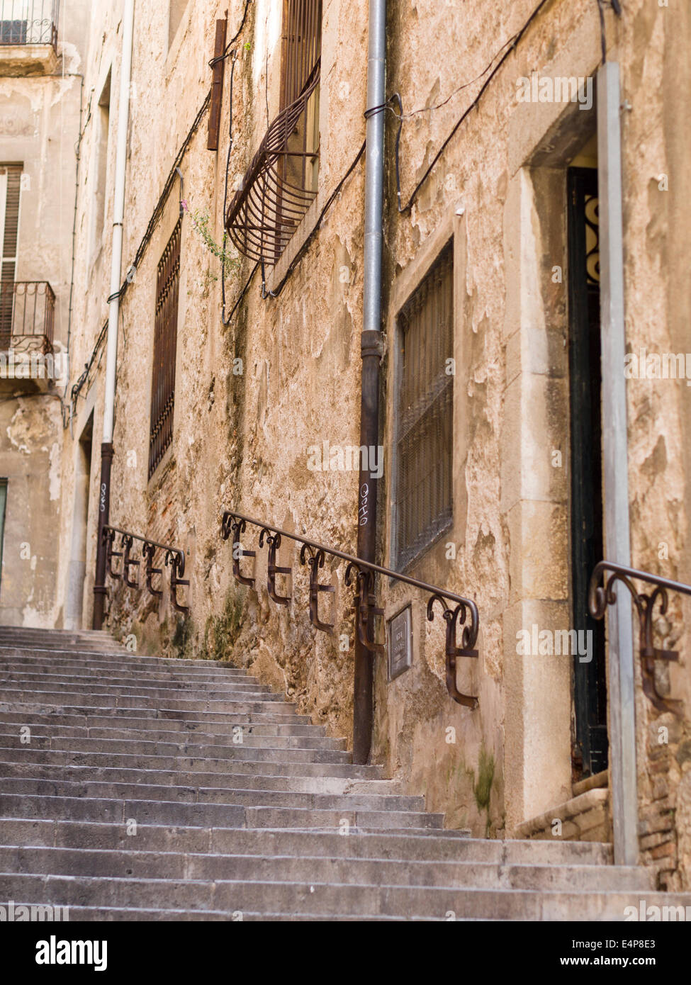 Girona Steep Street Stair. A stone staircase in the old town ghetto of Girona. Iron handrails help with the climb. - Stock Image