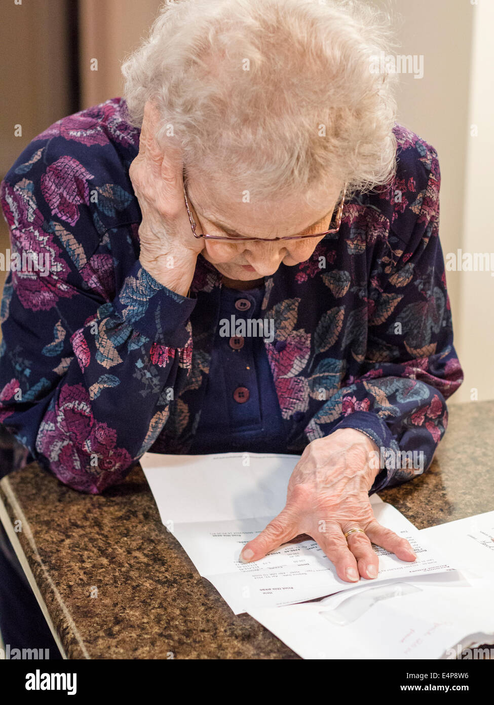 Trying to Understand a Letter. A senior woman reads a letter with her head held up by one hand while her other marks - Stock Image