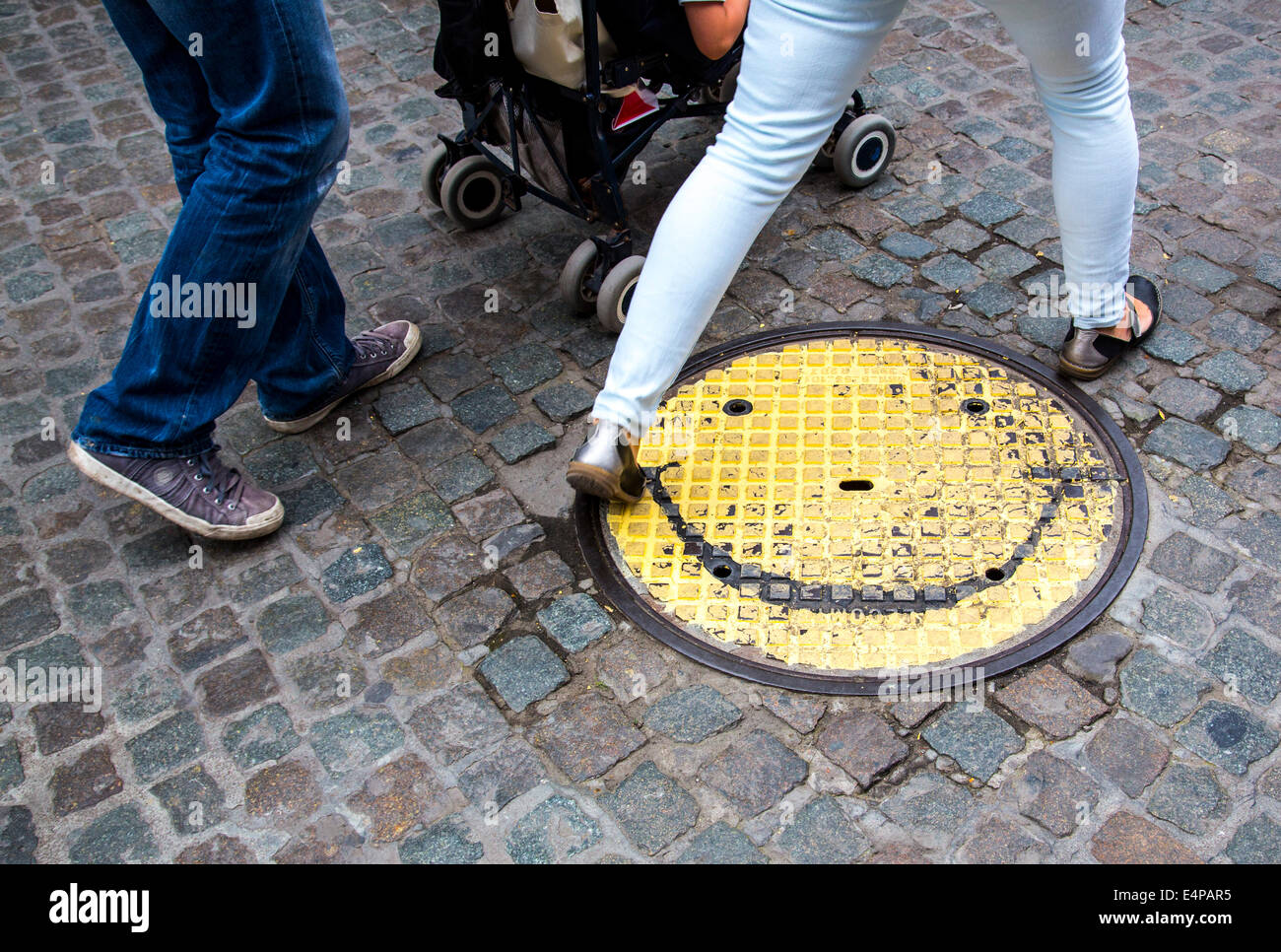 Manhole cover with a smily face painted, - Stock Image