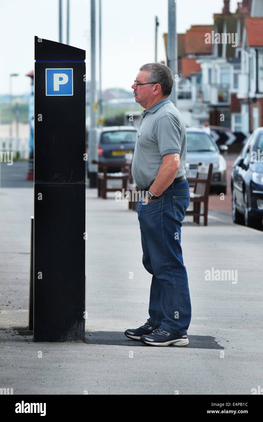 Man looking at vehicle parking charges on sea front. - Stock Image