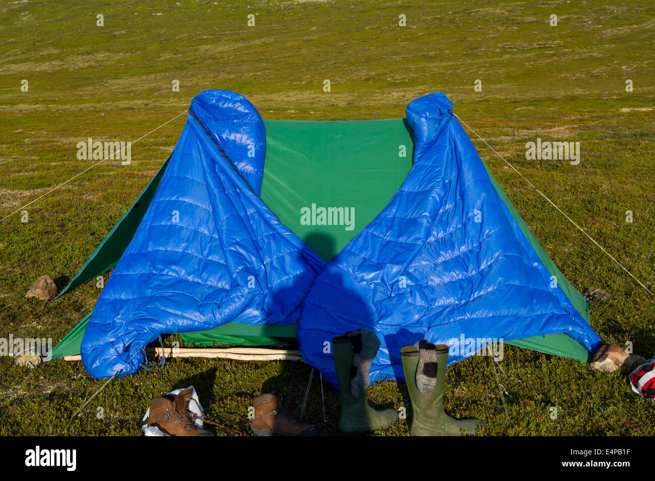 Shadow from a trekker on his tent with two sleeping bags hanging up to dry in the morning sun - Stock Image