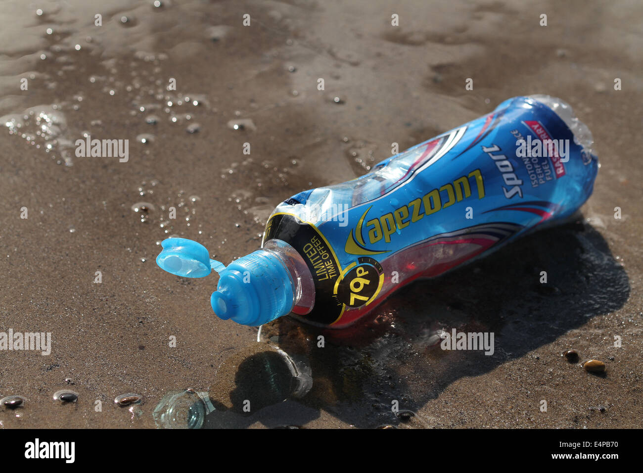 Plastic drinks bottle discarded on beach. - Stock Image