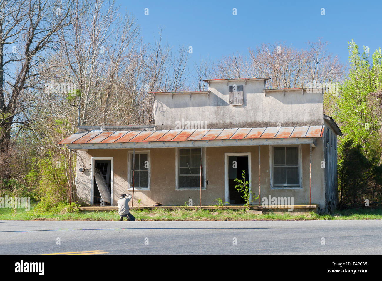 Photographer taking a picture of an old abandoned house. - Stock Image