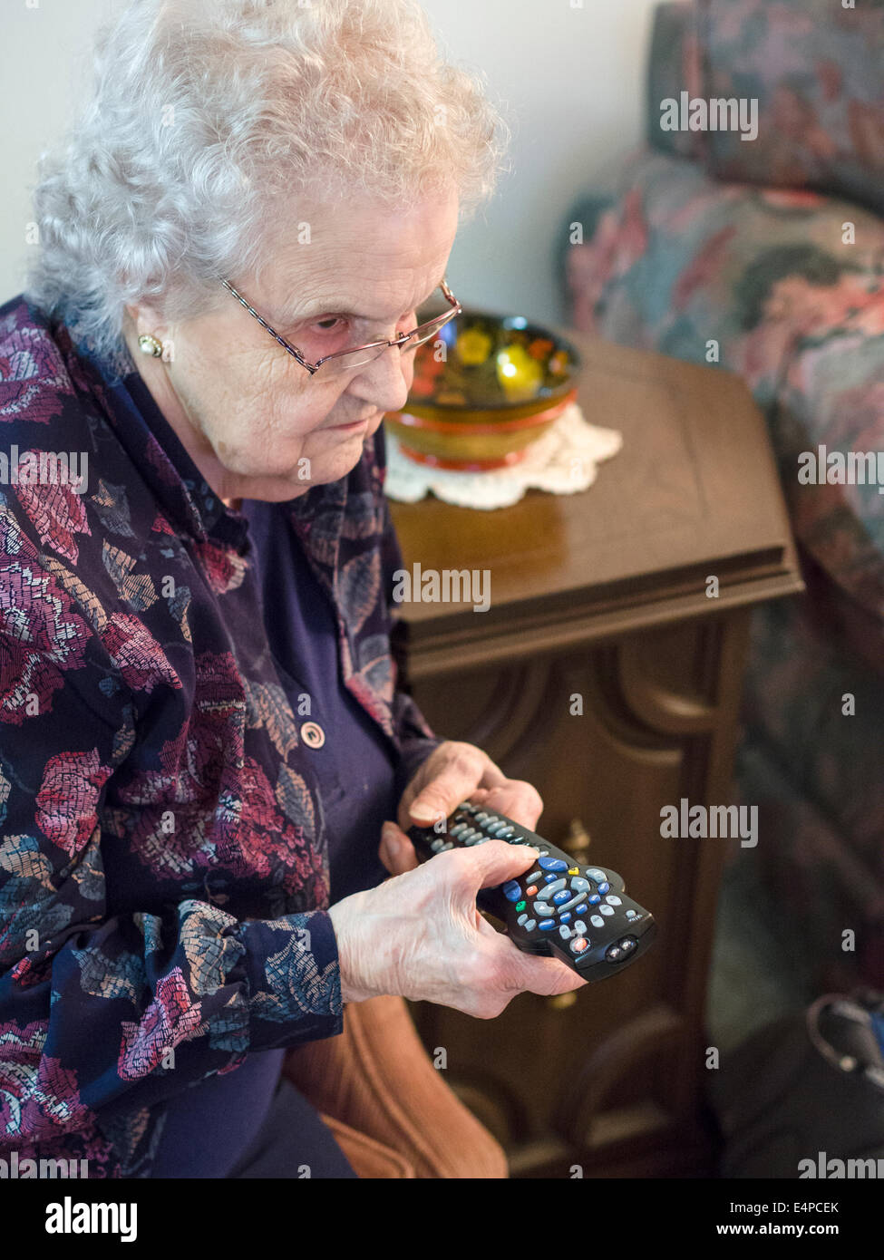 Learning the TV Remote . A senior woman adjusts her TV with a complicated remote control.  Ottawa, Ontario, Canada Stock Photo