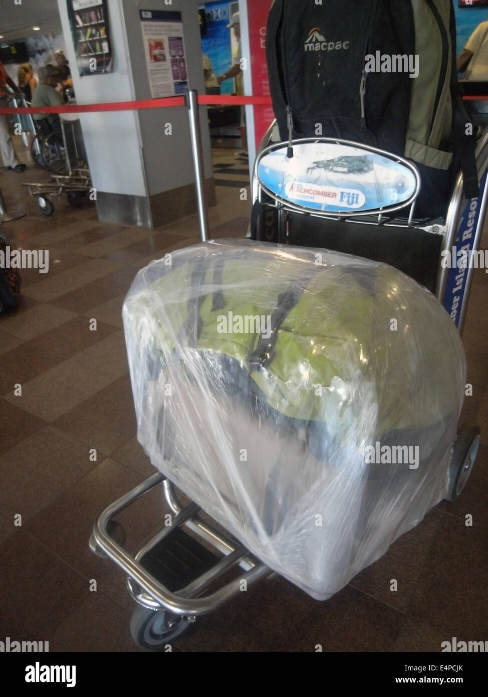 Two bags on trolley converted into one by plastic wrap to save on baggage restrictions, Nadi Airport, Fiji. No MR - Stock Image