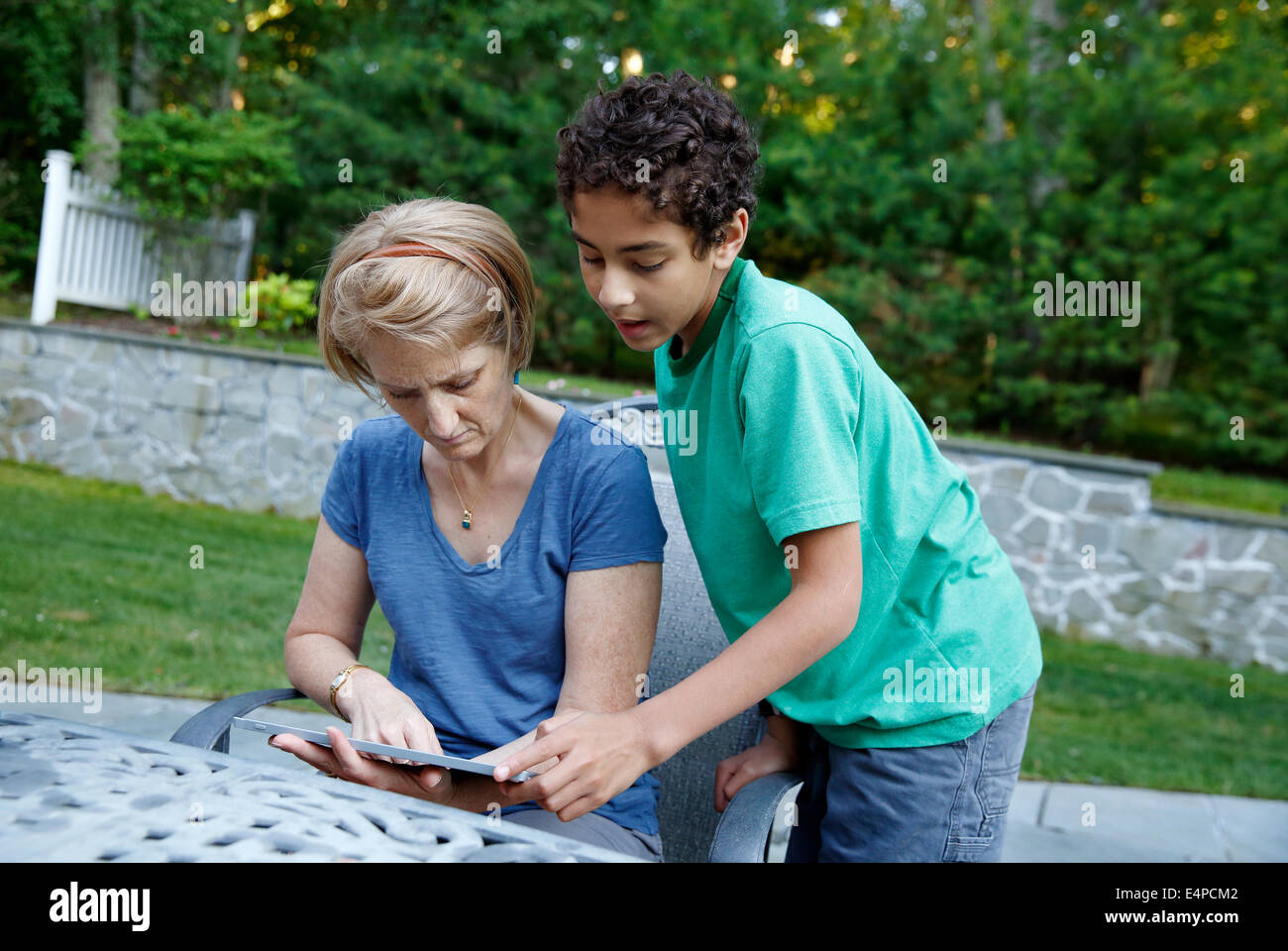 A boy shows his mother how to use a tablet computer - Stock Image