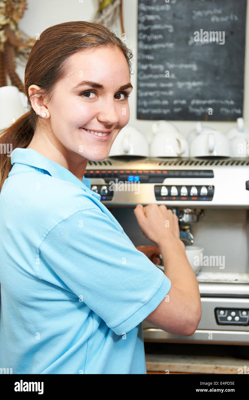 Woman In Cafe Making Cup Of Coffee - Stock Image