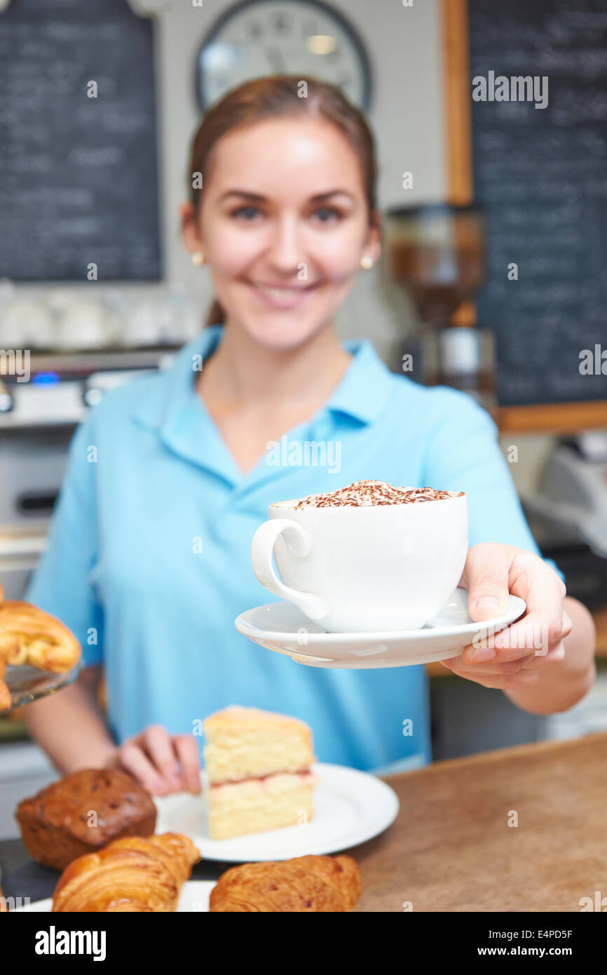 Waitress In Cafe Serving Customer With Coffee - Stock Image
