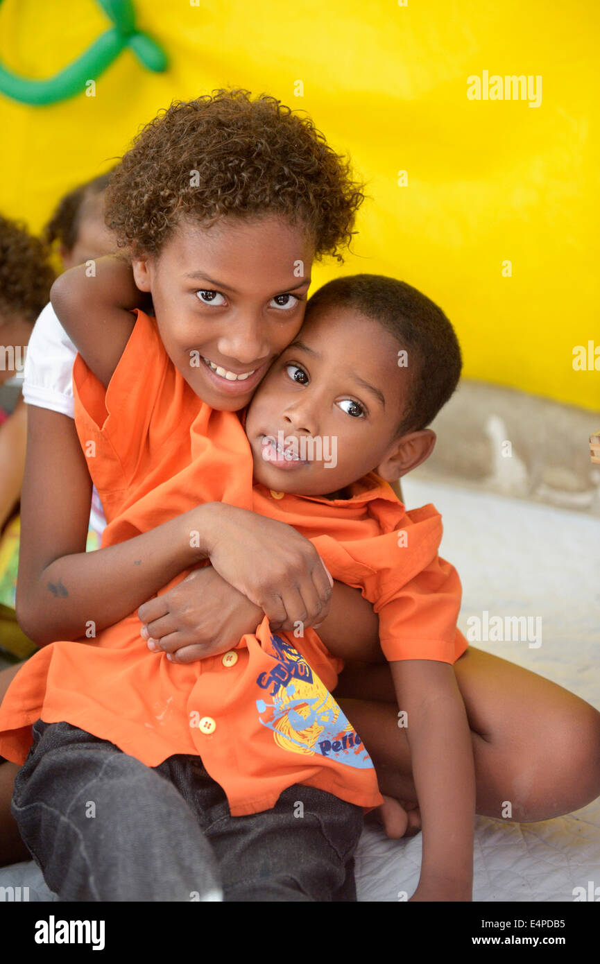 Girl, 9 years, and boy, 6 years, embracing each other, kindergarten of a social project, slum, Mangueirinha favela - Stock Image