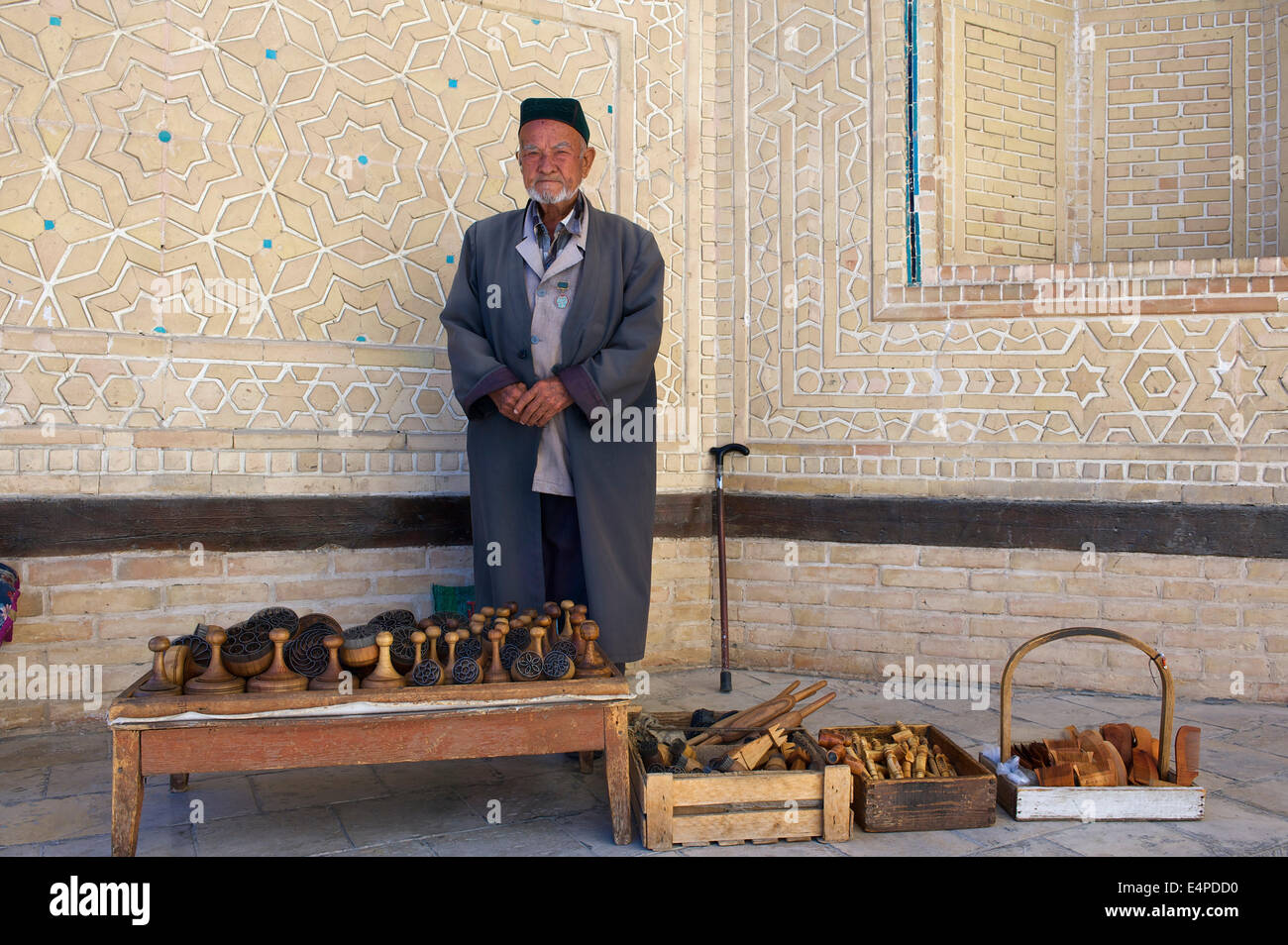 Local man with bread stamps in front of the Kalon Mosque, Bukhara, Uzbekistan Stock Photo