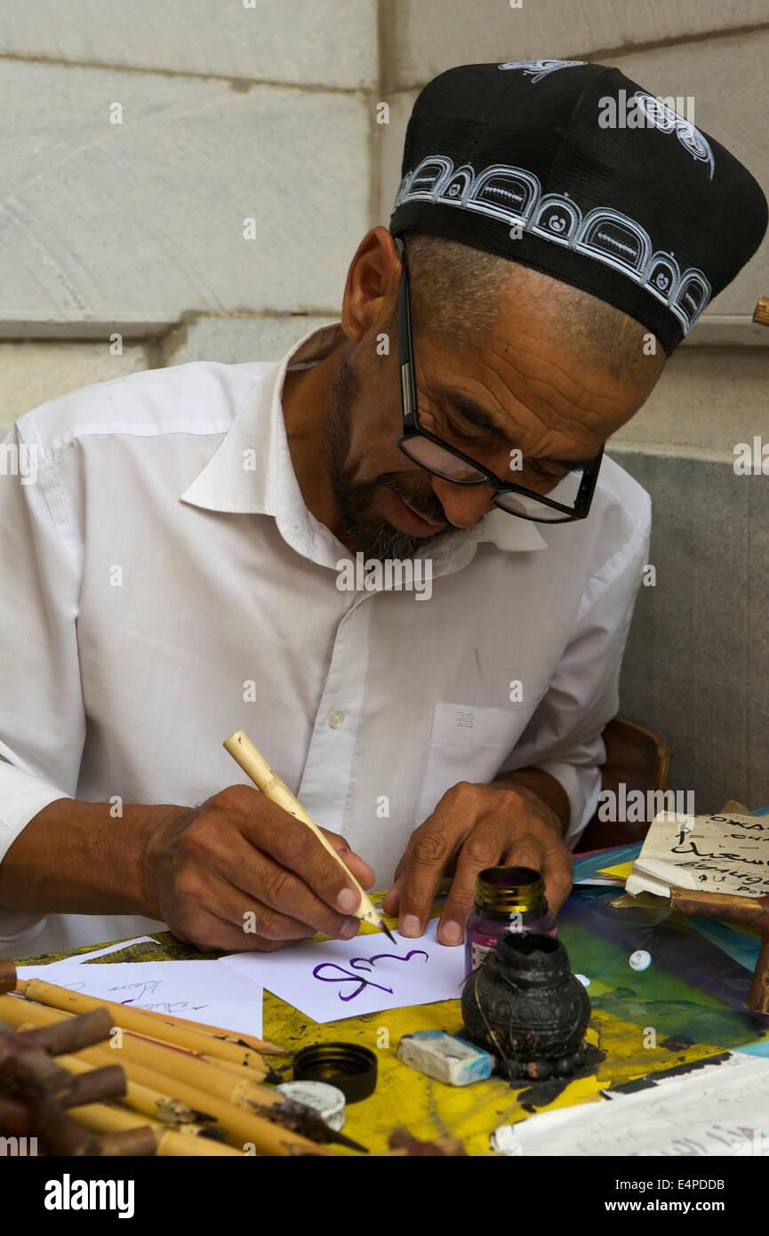Calligrapher in the Ulugbek Madrasah, Registan, Samarkand, Uzbekistan Stock Photo