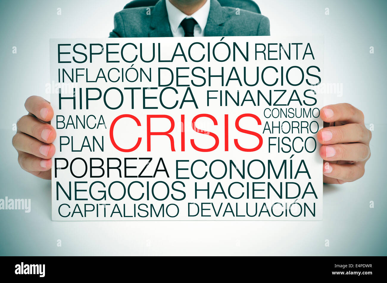 a businessman holding a signboard with different terms in spanish related to the economic crisis concept - Stock Image