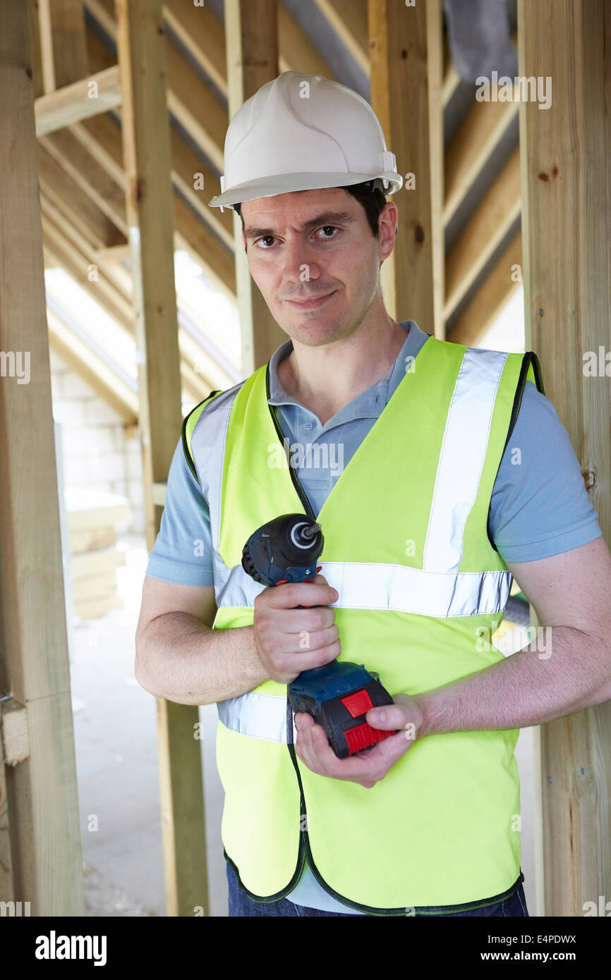 Builder On Construction Site Holding Cordless Drill - Stock Image
