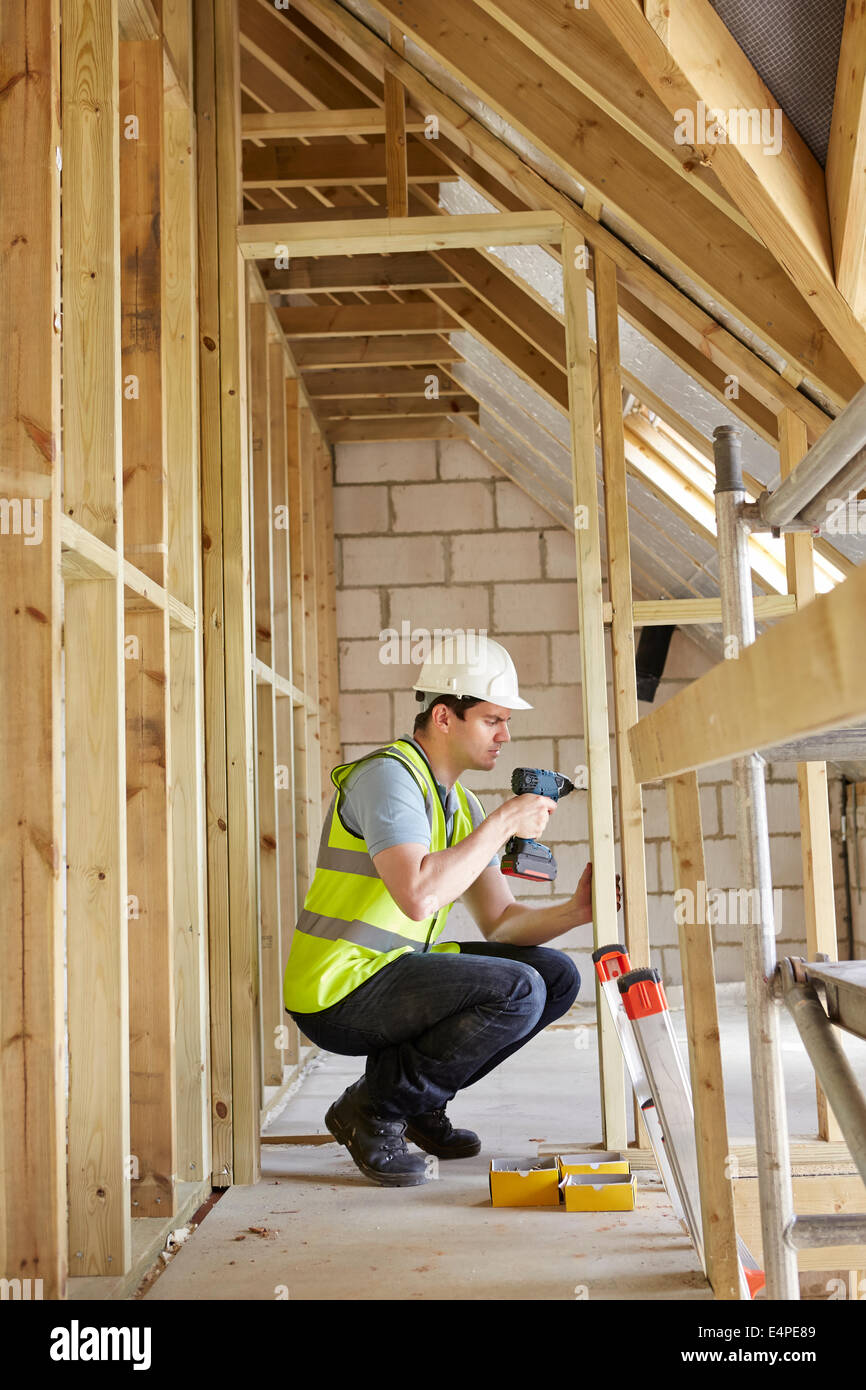 Construction Worker Using Drill On House Build - Stock Image