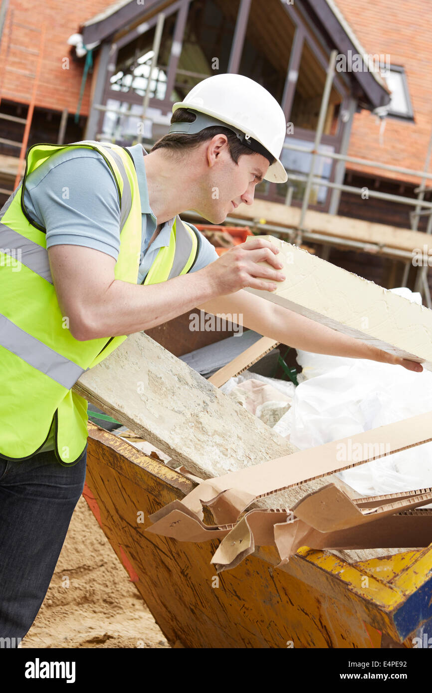 Builder Putting Waste Into Rubbish Skip - Stock Image