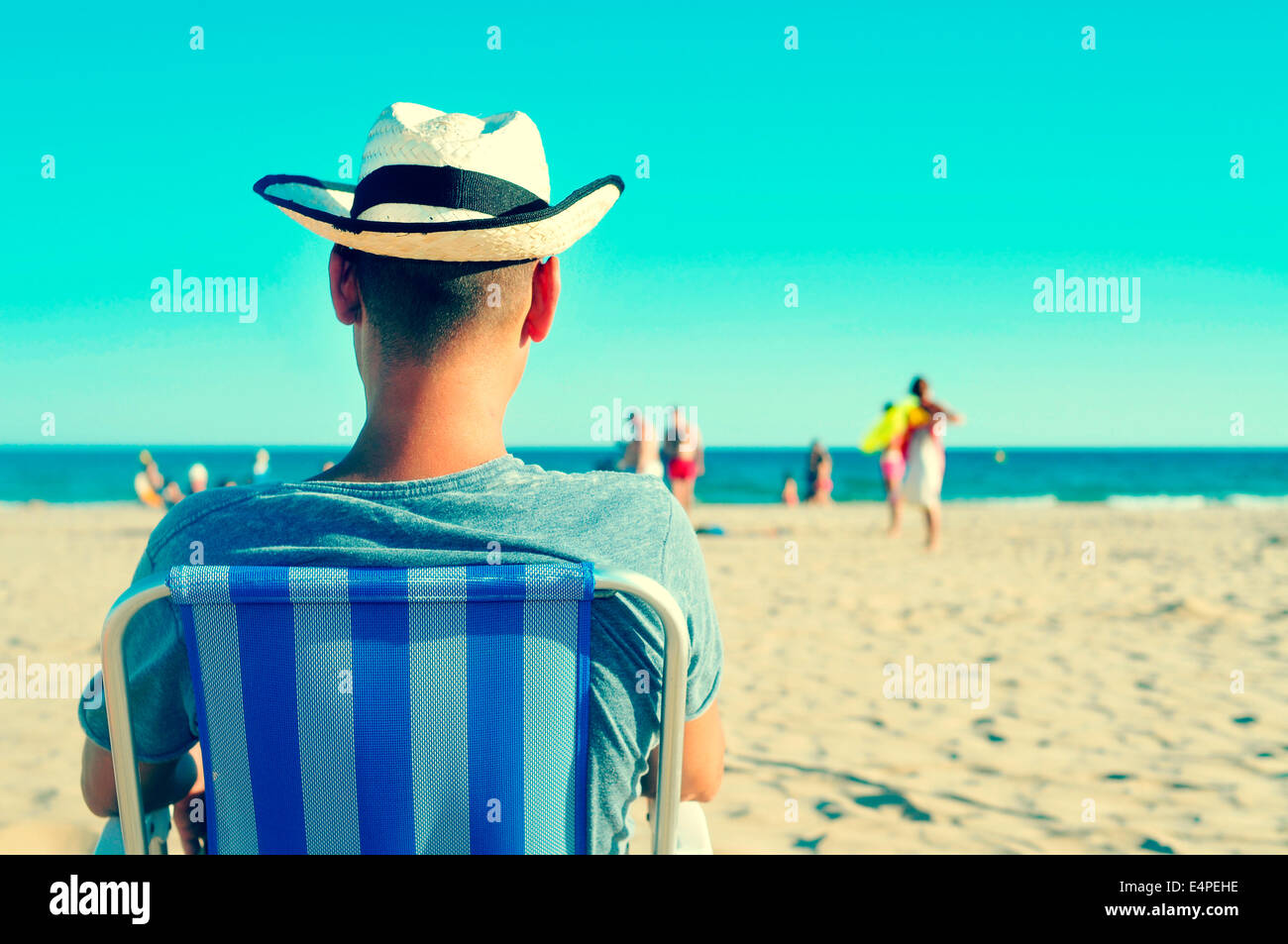 a young man with a straw hat relaxing on the beach - Stock Image