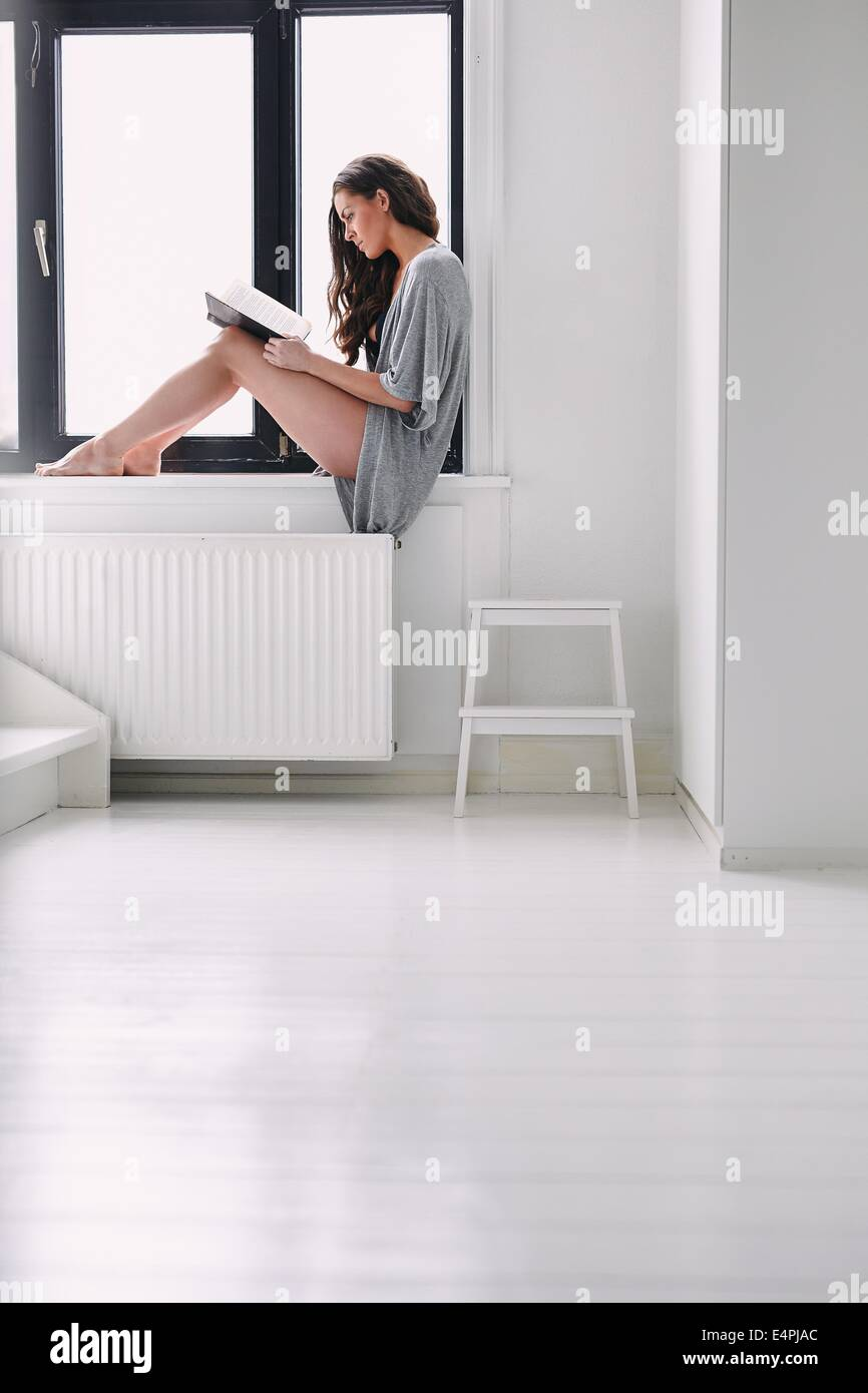 Indoor shot of young woman sitting on window sill and reading a book. Caucasian female model in nightwear busy reading - Stock Image