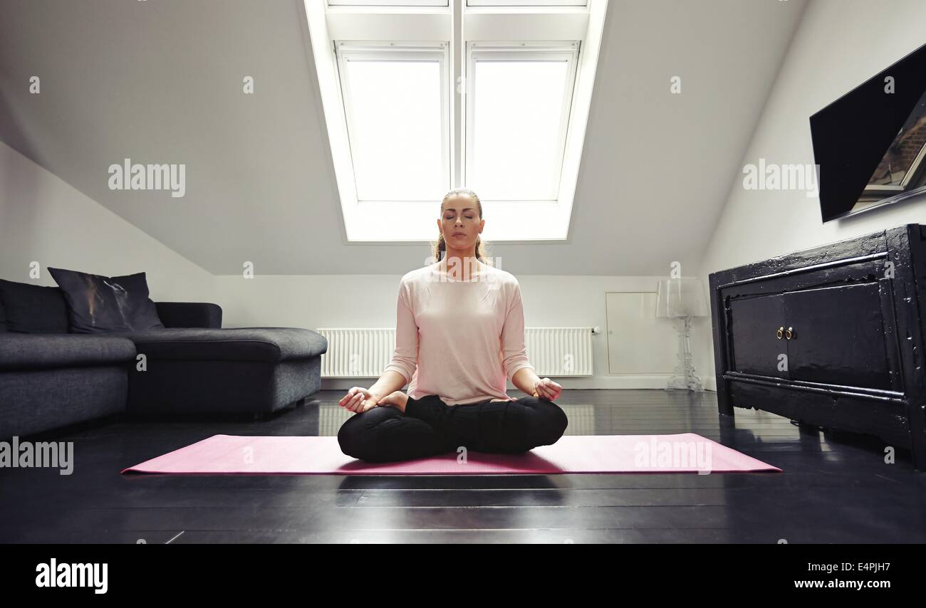 Portrait of young woman meditating in lotus position at home. Caucasian female model sitting with legs crossed on - Stock Image