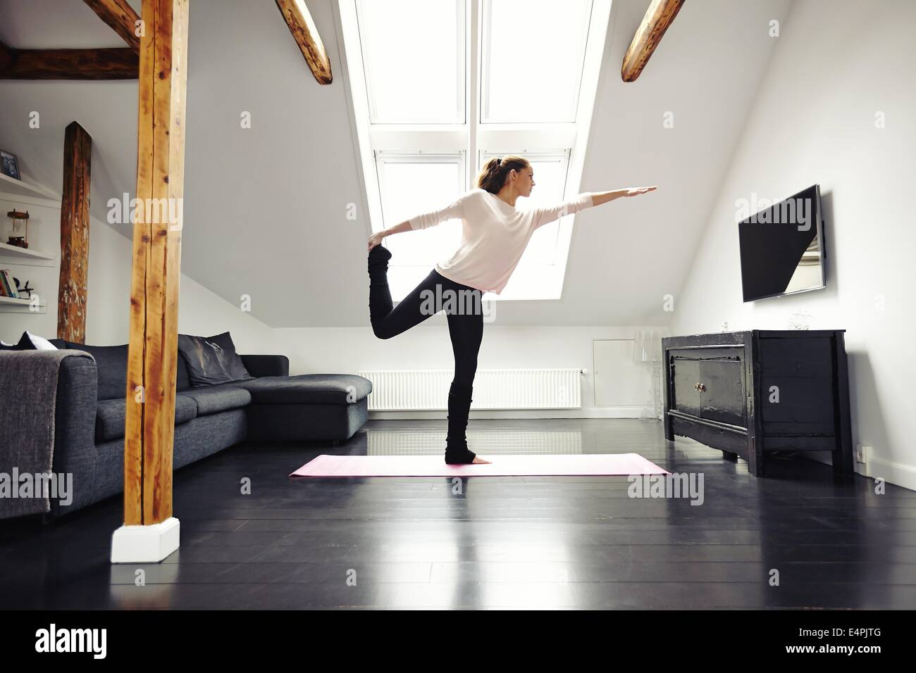 Fitness female exercising in living room. Stretching and balancing on one leg at home. Caucasian female practicing - Stock Image