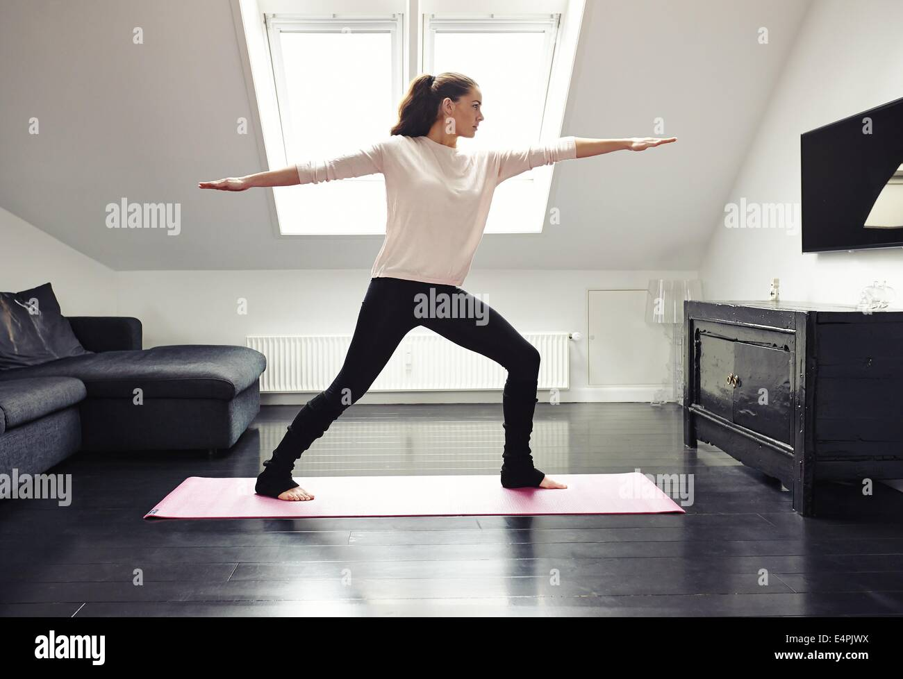 Portrait of a young woman doing yoga on an exercising mat in her living room. Caucasian female model in warrior - Stock Image